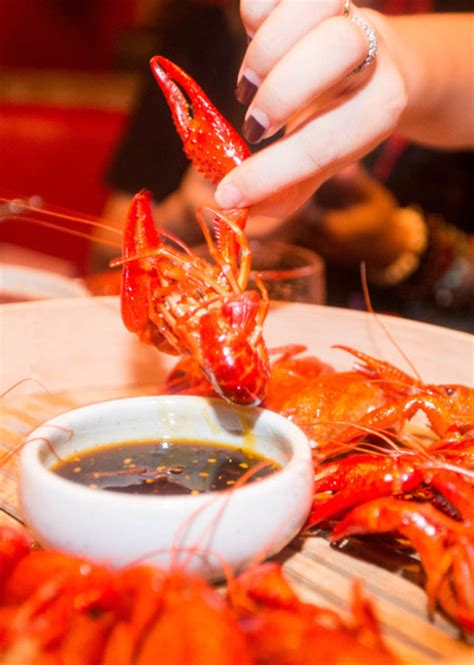 a diner enjoys a popular dish of crayfish with spicy sauce